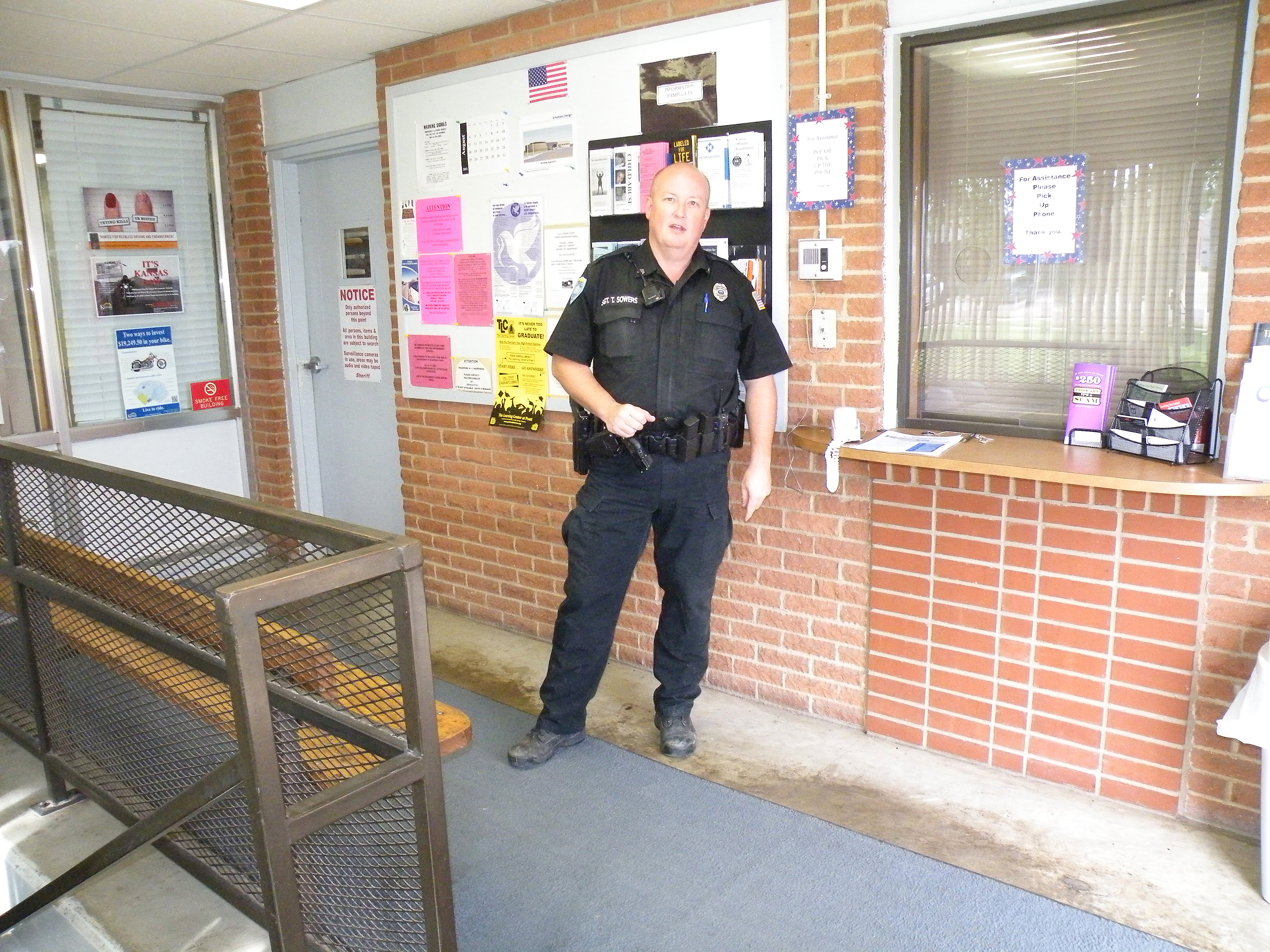 A uniformed police officer standing in front of a bulletin board